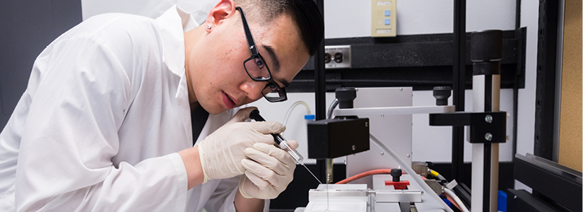 photo of a student performing an experiment in a lab.